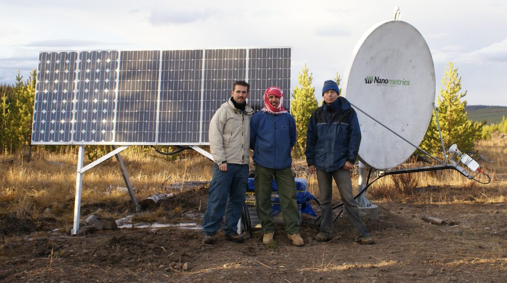 Three men stand before an array of solar panels and a satellite dish.