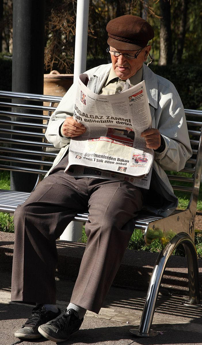 Man reading newspaper on park bench.