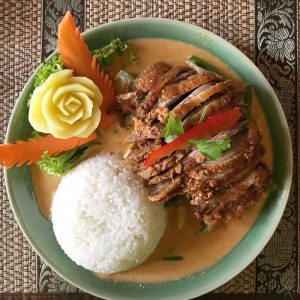 """A chicken and rice meal is beautifully arranged on a plate."""" title=""""A chicken and rice meal is beautifully arranged on a plate."""