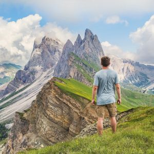 "A man stands in an alpine meadow and looks into the distance at the high mountain peaks."" title=""A man stands in an alpine meadow and looks into the distance at the high mountain peaks."