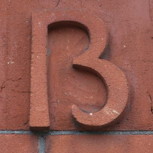 "Close up image of the marking on the side of a building. It isn't clear if the marking is the number 13 or the letter B."" title=""Close up image of the marking on the side of a building. It isn't clear if the marking is the number 13 or the letter B."