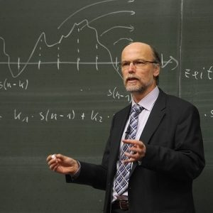 A stereotypical image of a professor - a white, middle-aged man with glasses and a beard, dressed in a coat and tie stands with chalk in hand in front of a blackboard which displays a mathematical formula.