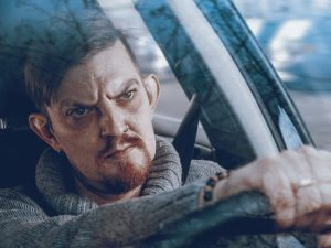 A man with an angry expression on his face sits behind the wheel of a car staring straight ahead.