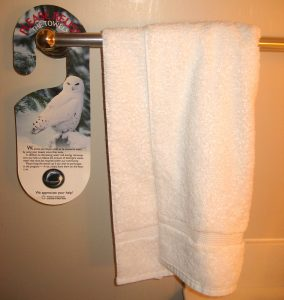A towel rack in a hotel guest bathroom has a white towel hanging next to an informational sign about how to save water.
