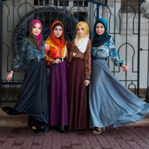A group of Malaysian fashion models pose in colorful headscarves, long-sleeve blouses, and floor-length dresses.