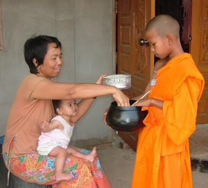 A Buddhist woman with a baby in her lap places food into the alms bowl of a young Buddhist priest dressed in traditional orange robes.