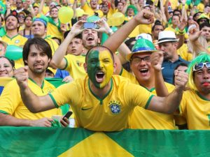 Brazilian soccer fans dressed in the colors of the national team cheer wildly from the stands during a match.