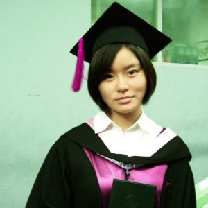 A East Asian woman dressed in a graduation cap and gown wears a neutral or subdued expression.