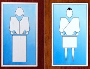 Restroom signs from the country of Bhutan display stylized representations of a woman and a man dressed in traditional clothes.