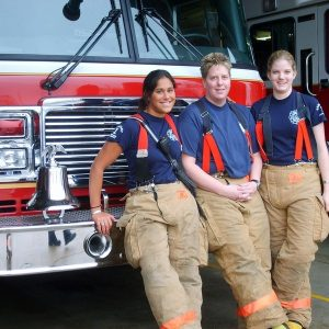 Three female members of a fire and rescue team stand in front of a fire engine wearing firefighting safety clothing.