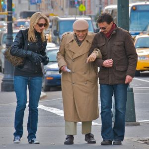 A younger man and woman helping an elderly gentleman down the street.
