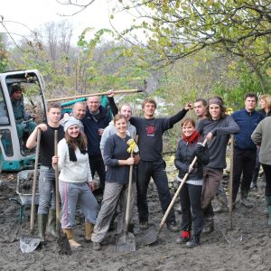 A group of men and women stand together in a muddy field with shovels and wheelbarrows as they participate in an outdoor volunteer project.