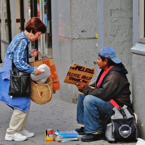 A woman stops on the sidewalk to offer food to a man holding a sign reading 'Homeless, please help Thank you.'