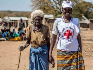 A Red Cross volunteer assists an elderly woman from Mozambique, where a food distribution was taking place.