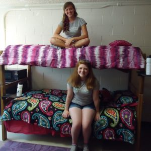 Two college students sit on bunk beds in a very clean and orderly dorm room.