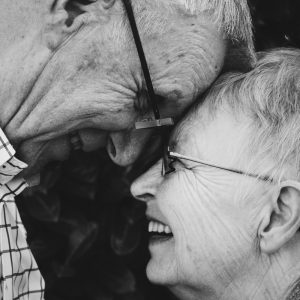 An elderly couple embrace and look into each other's eyes.