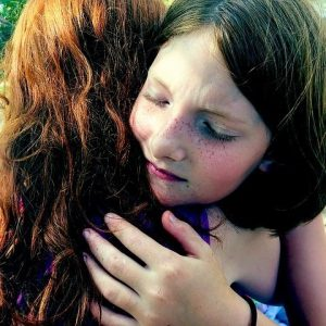 A girl closes her eyes as she hugs her friend.