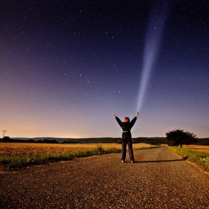 A woman stands in the middle of a country road at night and reaches towards the star-filled sky at night.