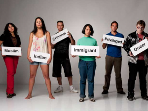 A group of people stand holding signs labeling them as others perceive them. The signs include, 'Muslim', 'Indian', 'Criminal', 'Immigrant', 'Privileged', and 'Queer'.