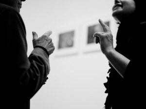 A man and woman are engaged in a conversation and making identical hand gestures.