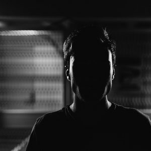 A man stands in a darkened room with his face almost entirely obscured by shadow.