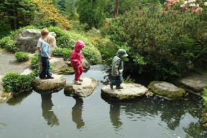 Four children walking on stepping stones to get accross a small pond.