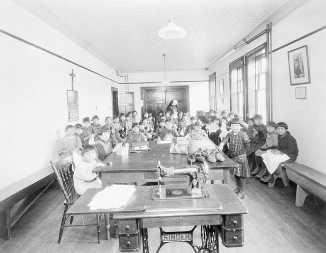 Young aboriginal students sit on benches in a crowded classroom.