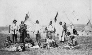 A Blackfoot tribe gathered in front of teepees.