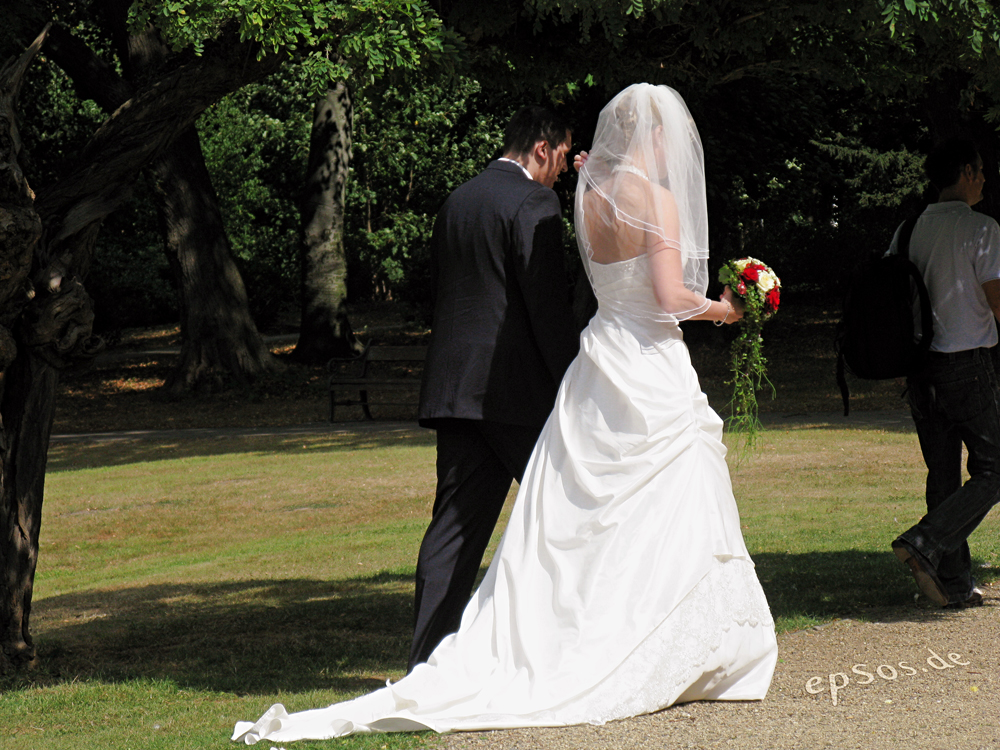 A bride and groom holding hands walking through a park.