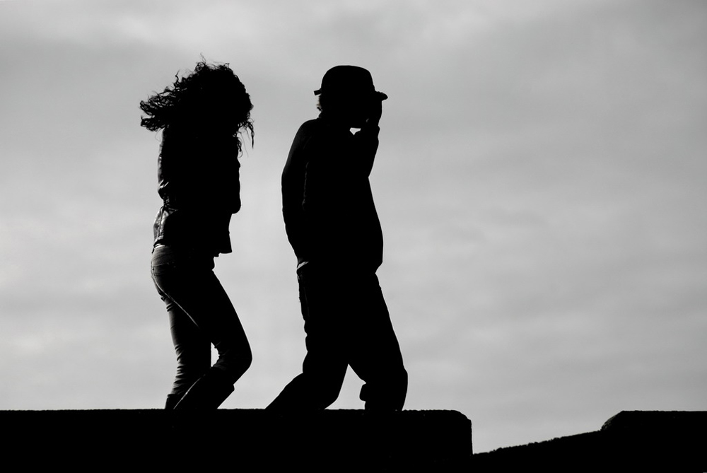 A man and woman are shown walking in the wind, man in front of woman.