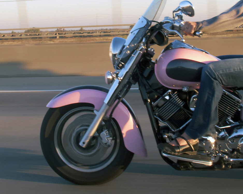 A woman riding a pink motorcycle.