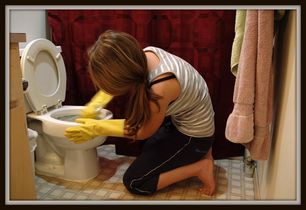 A woman kneeling on bathroom floor scrubbing a toilet.