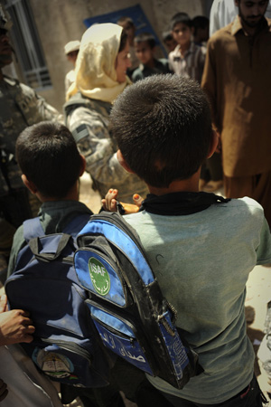 A young boy carrying a backback with an ISAF logo on it.