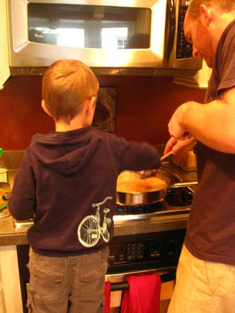 A young boy stands at a stove beside a man helping stir a pot.