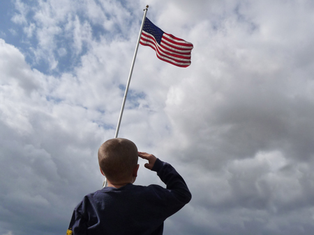 A young boy salutes the American flag.