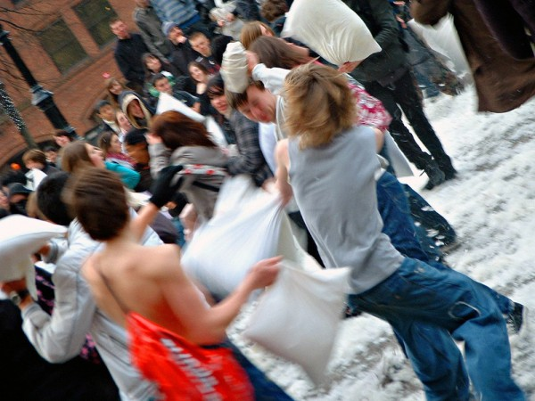 A large pillow fight on the street.