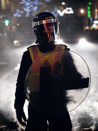 A police officer wearing riot gear including a helmet, a bright vest, and a shield.