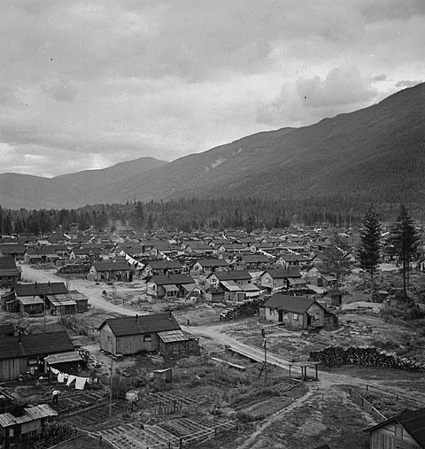 A black and white photo taken from above shows many small houses in a mountain valley