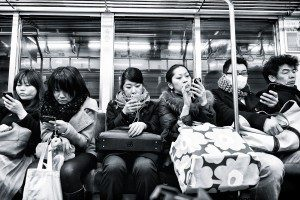 A group of people sitting on a subway, all on their cell phones.