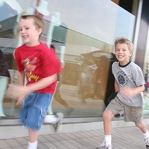 Two young boys sprint along a sidewalk.