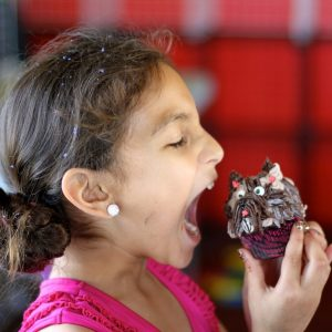 A girl prepares to take a big bite out of a cupcake.