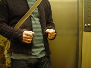 A man nervously clutches his fists inside an elevator.