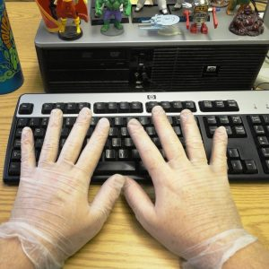 A man wears latex gloves while typing.
