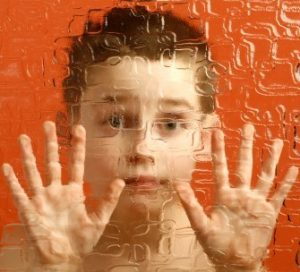 A boy looks out from behind textured glass.