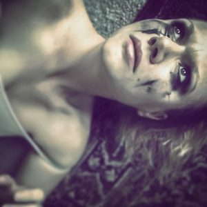 """A distraught looking woman lies on the floor with makeup smeared across her face."""" title=""""A distraught looking woman lies on the floor with makeup smeared across her face."""