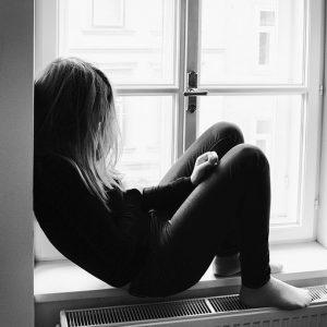 A young women sits alone on a windowsill.