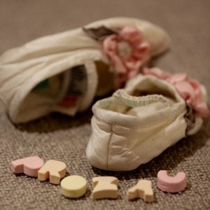 "Image of baby booties and the word 'Prozac' spelled out in candy letters."" title=""Image of baby booties and the word ""Prozac"" spelled out in candy letters."