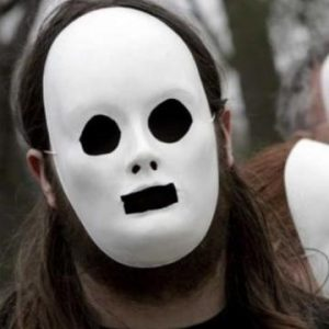 A man is seen wearing an expressionless white plaster mask with black eyes and mouth.