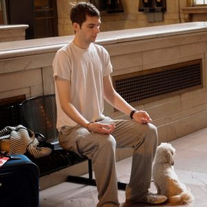 "A young man meditates on a bench in a train station."" title=""A young man meditates on a bench in a train station."