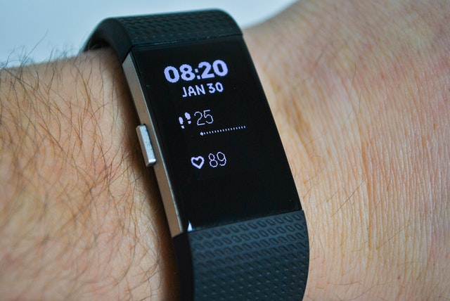 Photo of a Fitbit Charge HR on a person's wrist displaying time, steps taken, and heart rate.
